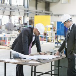 Businessmen examining blueprint at workbench in metal industry